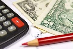 Fragmento de la calculadora electrónica, de los dólares de EE. UU. de billetes de banco y del lápiz rojo Foco en la esquina de un Imagen de archivo
