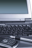 Fragmento de la computadora portátil con un teléfono móvil y una pluma Foto de archivo libre de regalías