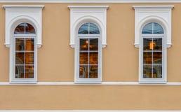Fragmento de la fachada del edificio viejo después de la reconstrucción, con tres el arquear-tipo blanco ventanas imagen de archivo libre de regalías
