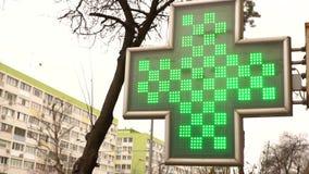 Fragmento de la farmacia en la calle de la ciudad Iluminación de la cruz de la farmacia y de un estetoscopio almacen de metraje de vídeo