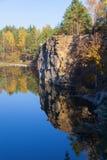 Fragmento de la orilla del lago con la piedra en bosque del otoño Imagen de archivo libre de regalías