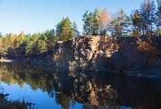 Fragmento de la orilla del lago con la piedra en bosque del otoño Imagenes de archivo
