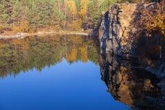 Fragmento de la orilla del lago con la piedra en bosque del otoño Fotografía de archivo