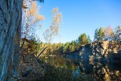Fragmento de la orilla del lago con la piedra en bosque del otoño Imagen de archivo