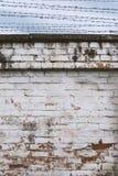 Fragmento de la pared de ladrillo vieja resistida con el alambre de púas, fondo del cielo Foto de archivo