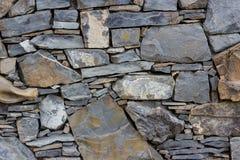 Fragmento de la pared hecha de piedras de diversos tipos y forma Foto de archivo libre de regalías