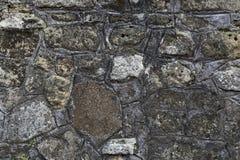 Fragmento de la pared de piedra gris vieja hecha de diversas rocas de la forma y del tamaño con el musgo verde en él foto de archivo