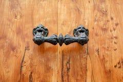 Fragmento de la puerta principal de madera clásica con el tirador de puerta decorativo figurado foto de archivo