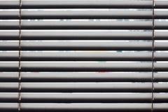 Fragmento de las persianas blancas con el cordón de la elevación y la barra de torneado de un control manual en un primero plano Fotografía de archivo