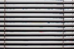 Fragmento de las persianas blancas con el cordón de la elevación y la barra de torneado de un control manual en un primero plano Foto de archivo