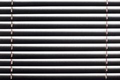 Fragmento de las persianas blancas con el cordón de la elevación y la barra de torneado de un control manual en un primero plano Foto de archivo libre de regalías