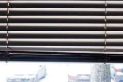 Fragmento de las persianas blancas con el cordón de la elevación y la barra de torneado de un control manual en un primero plano Imágenes de archivo libres de regalías