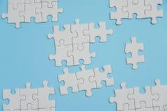 Fragmento de um enigma de serra de vaiv?m branco dobrado e uma pilha de elementos uncombed do enigma na perspectiva de uma superf fotos de stock