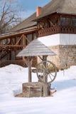 Fragmento de um pátio da vila com um poço de madeira e de uma casa no museu nacional da vila Bucareste, Romania fotos de stock royalty free