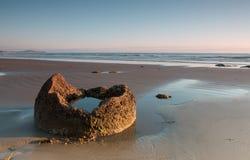 Fragmento de un canto rodado en la orilla del océano en la salida del sol Foto de archivo