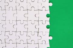 Fragmento de un rompecabezas blanco doblado en el fondo de una superficie plástica verde Foto de la textura con el espacio de la  foto de archivo