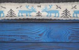 Fragmento de una bufanda hecha punto en una superficie de madera azul Foto de archivo libre de regalías
