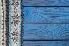 Fragmento de una bufanda hecha punto en una superficie de madera azul Imagenes de archivo