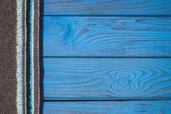 Fragmento de una bufanda hecha punto en una superficie de madera azul Foto de archivo