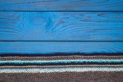 Fragmento de una bufanda hecha punto en una superficie de madera azul Fotos de archivo