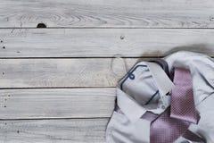 Fragmento de una camisa del ` s de los hombres con un lazo en una suspensión en un pai de madera Imagen de archivo libre de regalías
