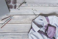 Fragmento de una camisa del ` s de los hombres con un lazo en una suspensión y un diario en a Fotografía de archivo libre de regalías