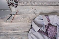 Fragmento de una camisa del ` s de los hombres con un lazo en una suspensión y un diario en a Imágenes de archivo libres de regalías