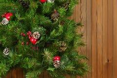 Fragmento del árbol de navidad adornado verde en fondo de madera Fotos de archivo