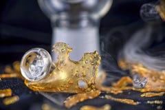 Fragmento del concentrado del aceite de la marijuana aka aislado con el aparejo de cristal encendido fotografía de archivo libre de regalías
