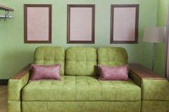 Fragmento del interior con un sofá verde y las tarjetas de imagen fotos de archivo libres de regalías