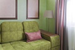 Fragmento del interior con un sofá verde y las tarjetas de imagen imagen de archivo libre de regalías