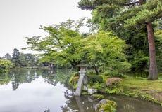 Fragmento del jardín japonés con la linterna de piedra y el rocho cubierto de musgo grande Imagen de archivo libre de regalías