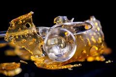 Fragmento do concentrado do óleo do cannabis aka com as ferramentas de vidro isoladas fotos de stock