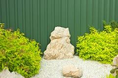 Fragmento do jardim com arbustos verdes e as pedras brilhantes Fotos de Stock Royalty Free
