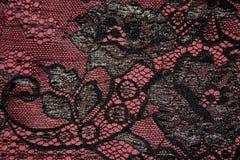 Fragmento do laço preto contra a cor de Borgonha do fundo fabuloso Fotografia de Stock