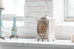 Fragmento interior elegante lamentable ligero con el reloj y las palmatorias imagen de archivo libre de regalías