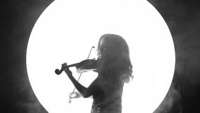 Fragmento video blanco y negro de una muchacha hermosa que toca el violín en un fondo blanco del círculo en el humo almacen de metraje de vídeo
