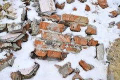 Fragmentos del ladrillo rojo, cubiertos con nieve fotografía de archivo