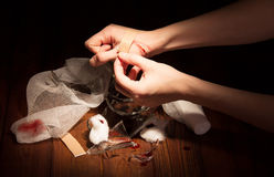 Fragments of broken glass, a wounded arm isolated on black. Fragments of broken glass, a wounded arm, patch and bandages isolated on a black background stock image
