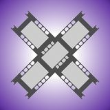 Vector illustration of two criss-cross fragments of film on a violet background. Flat design. Fragments of camera film on a violet background. Old film black Royalty Free Stock Photo