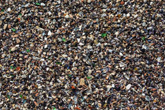 Fragments of glass intermixed with sand. Texture of colored stones Royalty Free Stock Photo