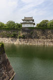 Fragments of Osaka Castle with big moat in the foreground in Osa Royalty Free Stock Image