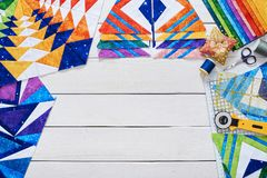 Fragments of quilt, accessories for patchwork, top view. On a white wooden surface with a copy space stock image