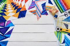 Fragments of quilt, accessories for patchwork, top view on a white wooden surface royalty free stock images