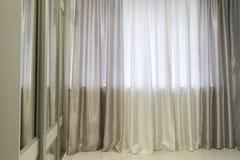 Fragments of silk curtains on  window Stock Photos