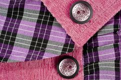Fragments of the texture of a children`s pink dress with buttons.  stock images