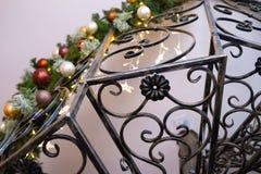 Fragmentschmiedeeisentreppenhaus mit dem verzierten Weihnachtsbaum im Innenraum und in den Lichtern lizenzfreie stockfotografie