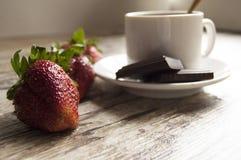 Fragola, cioccolato e una tazza di caffè su una vecchia tavola Fotografia Stock Libera da Diritti