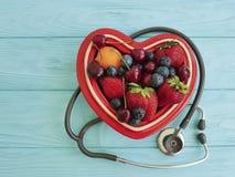 Fragola della frutta, mirtillo, ciliegia, cuore del piatto dell'albicocca su misto antiossidante dolce dello stetoscopio di legno fotografia stock