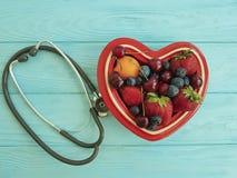 Fragola della frutta, mirtillo, ciliegia, cuore di idea del piatto dell'albicocca su misto antiossidante dolce dello stetoscopio  fotografia stock libera da diritti